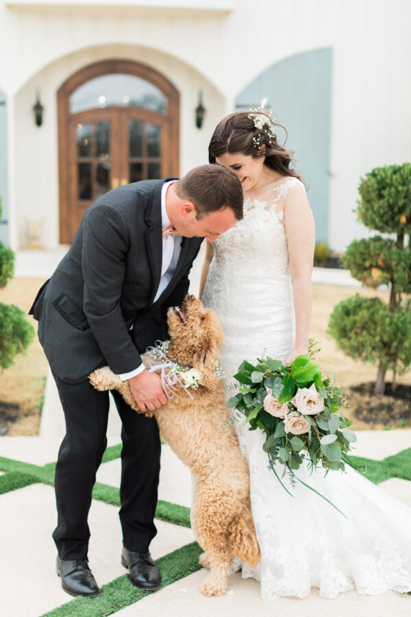 couple poses with their dog after their first look