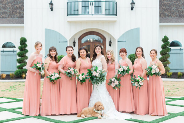 bride and bridesmaids pose in front of venue with brides dog