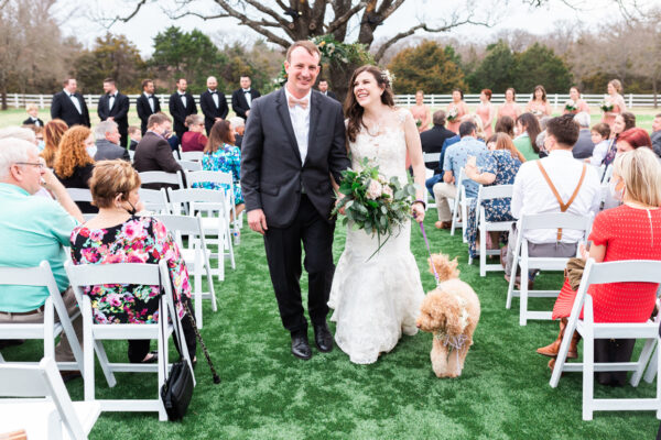 bride and groom walking down the aisle with couples dog
